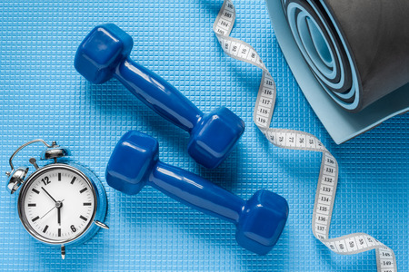 lifting weights: Blue yoga mat, two dumbbells, tape measure and alarm clock.