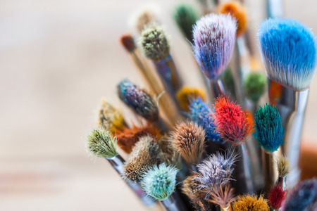 paint palette: Bunch of artist paintbrushes closeup, selective focus. Stock Photo