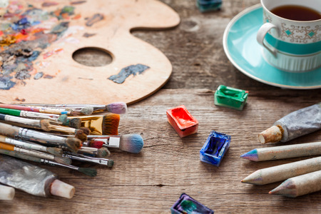 画家のブラシ、アーティスト パレット、鉛筆、コーヒー カップ、水彩や油絵の具画家スタジオの机の上。