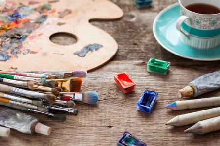 Farben, Pinsel, Künstlerpalette, Bleistifte, Kaffeetasse, Aquarell- und Ölfarben auf Schreibtisch im Maleratelier.