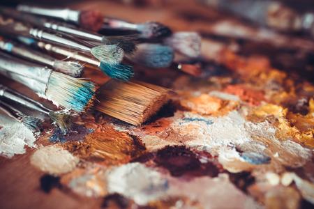 Paintbrushes closeup, artist palette and multicolor paint stains