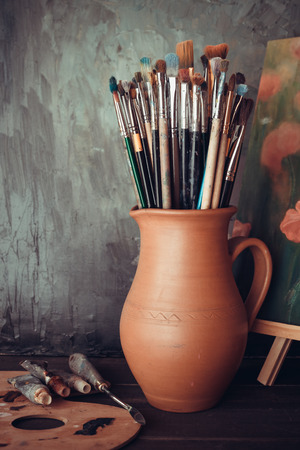 Paintbrushes in a jug from potters clay, palette, paint tubes and Painting in artist studio. Фото со стока