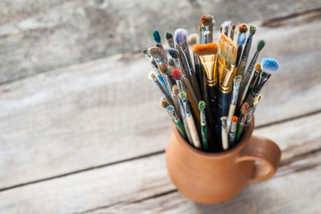 Used painter paintbrushes in a jug from potters clay photo