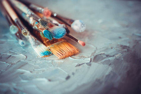 paint palette: Paintbrushes on artist canvas covered  with oil paints
