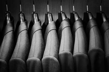 shirt hanger: Row of men suit jackets. Black and white image. Stock Photo