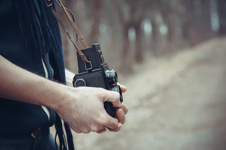 people  camera: retro stylized photo of young man photographer with vintage camera Stock Photo