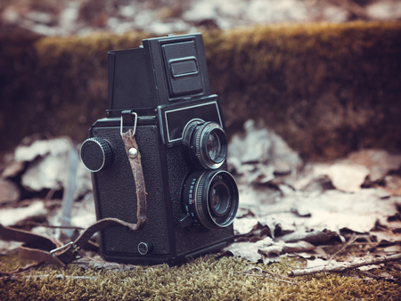 Vintage stylized photo of retro film camera on old stairs covered with leaves and moss photo