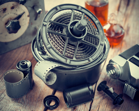 darkroom: Developing tank with its film reels, photo film rolls, cassette, retro camera and chemical reagents. Stock Photo