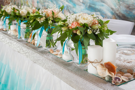 Beautiful bouquets of roses and decorations on table in wedding day.