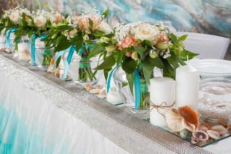 bodas de plata: Hermosos ramos de rosas y adornos en la mesa en día de la boda. Foto de archivo
