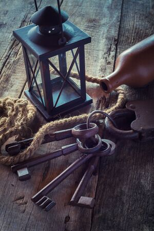 lighthouse keeper: Old rusty lock with keys, vintage lamp, bottle from clay and rope on wooden board. Retro stylized photo.