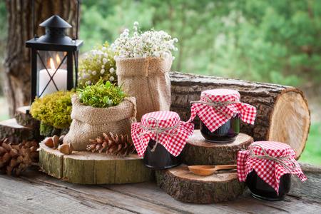 Bodegón con tarros de mermelada de frutas, lámpara de la vendimia y decoración de estilo rústico. Foto de archivo