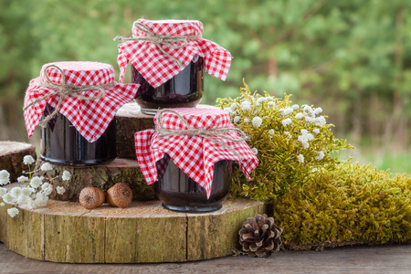arranging: Still life with three jars of jam and decoration in rustic style. Stock Photo
