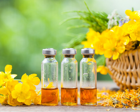 Bottles of healing plants treatment and healthy herbs in basket.
