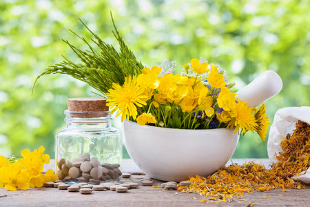 botanical remedy: Healing herbs in mortar and bottle of pills on rustic table, herbal medicine.