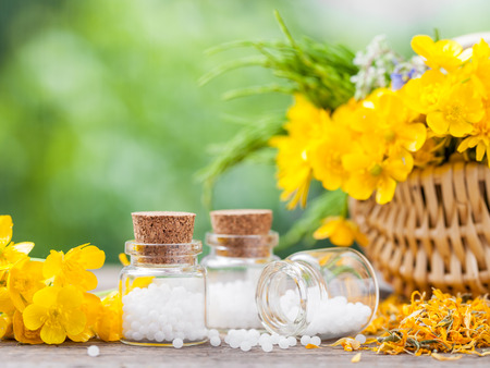 Bottles of homeopathy globules and healthy herbs in basket. Stockfoto