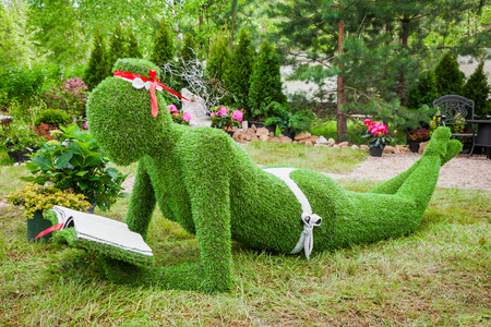 sculptures: Minsk, Belarus, 23-May-2015: Garden Sculpture from grass - woman with book on holiday in nursery Red maple. Minsk. Belarus.