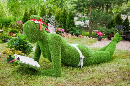 """Minsk, Wit-Rusland, 23-mei-2015: Garden Sculpture van gras - vrouw met boek op vakantie in de kwekerij """"Rode esdoorn"""". Minsk. Wit-Rusland. Redactioneel"""