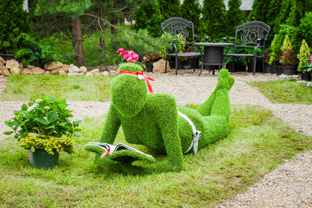 sculpture: Minsk, Belarus, 23-May-2015: Garden Sculpture from green grass - woman with book on holiday in nursery Red maple. Minsk. Belarus.