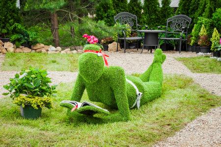 artificial flower: Minsk, Belarus, 23-May-2015: Garden Sculpture from green grass - woman with book on holiday in nursery Red maple. Minsk. Belarus.