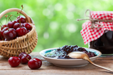 Basket with cherry, saucer and  jar of jam.