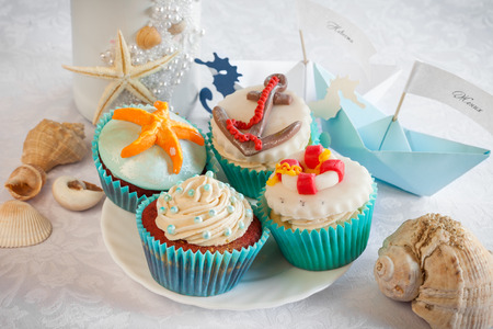 Wedding still life - cupcakes in nautical style, paper boats, vine bottle and sea shells on table.