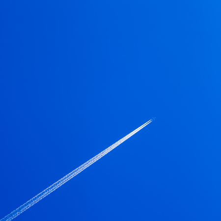 contrail: White contrail trace of plane on clear blue sky.