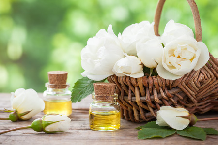 Wicker basket with white roses bunch and bottles of essential oil.