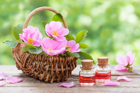 cesto di vimini rustico con rosa rosa fiori dell'anca e bottiglie di olio essenziale di rose. Archivio Fotografico