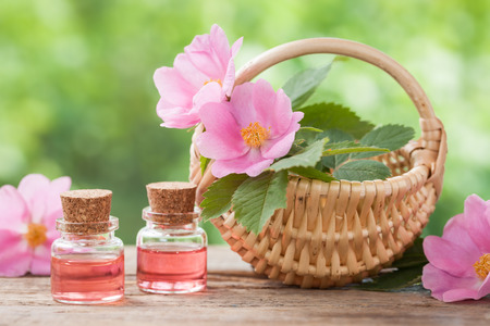 Rustic wicker basket with rose hip flowers and bottles of essential oil.