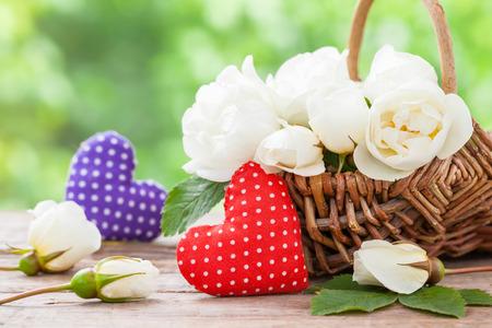 flores de cumpleaños: Cesta de mimbre con las flores salvajes y dos corazones de rosas. Boda o cumpleaños decoración en estilo rústico.