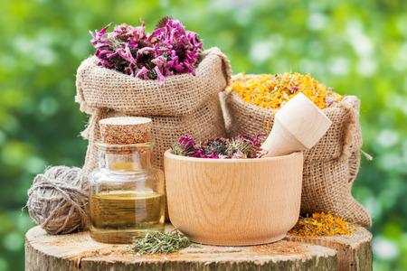 Healing herbs in hessian bags, wooden mortar with coneflowers and essential oil on wooden stump outdoors, herbal medicine. Stock Photo
