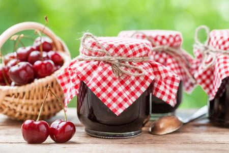 Marmeladengläser und Korb mit Kirschen.