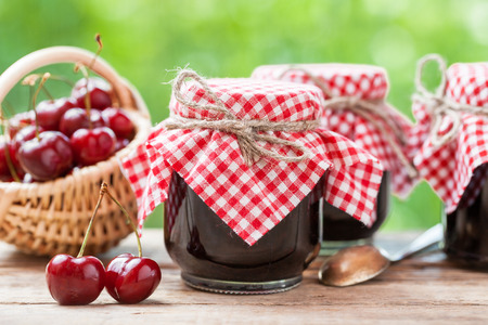 Jars of jam and basket with cherry.