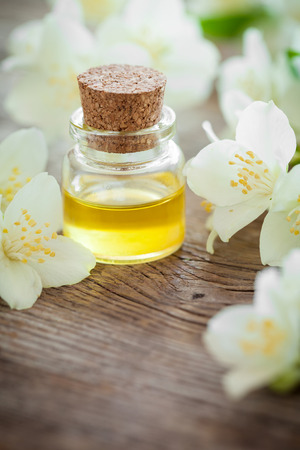 skin care products: Bottle of essential jasmine oil and white jasmin flowers. Stock Photo