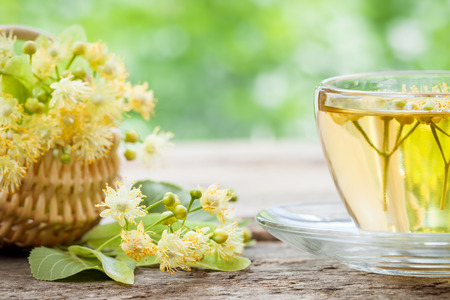 Cup of linden tea and wicker basket with lime flowers, herbal medicine. Stock Photo