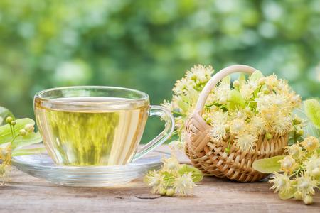 medicina: Taza de té de tilo saludable y cesta de mimbre con flores de limón, hierbas medicinales. Foto de archivo