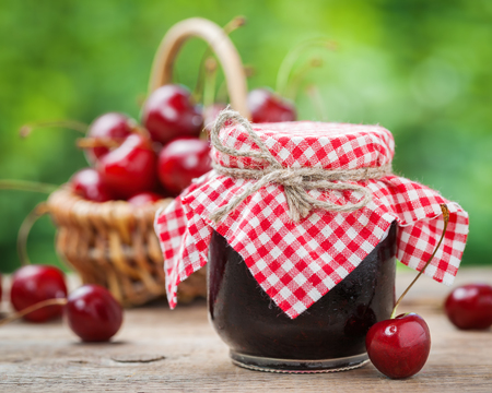 red gingham: Jars of jam and basket with cherry on background. Stock Photo