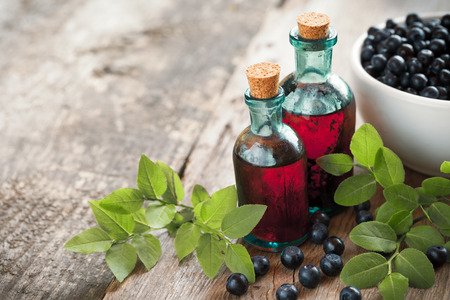 Bottles of tincture or cosmetic product and bowl with  blueberries on wooden table. 免版税图像