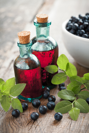 skin care products: Two vintage bottles of tincture or cosmetic product and bowl with blueberries on wooden table.