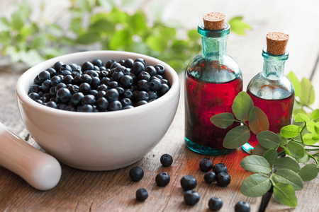cosmetic product: Mortar with blueberries and small bottles of tincture or cosmetic product. Selective focus.