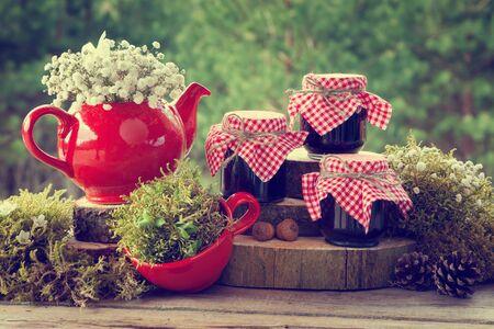 mermelada: Tetera roja, taza de té y botes de mermelada saludable. decoraciones de la boda en estilo rústico.