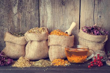 Geneeskrachtige kruiden in jute zakken en gezond kopje thee, kruiden medicine.Retro vormgegeven.