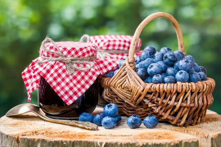 Panier avec les bleuets mûrs et deux pots de confiture Banque d'images - 43664129