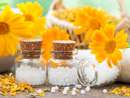 Three bottles of homeopathy globules and marigold flowers.