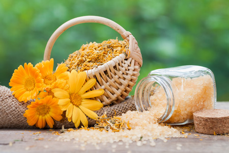 Marigold flowers, basket with dried plants and bottles of sea salt.