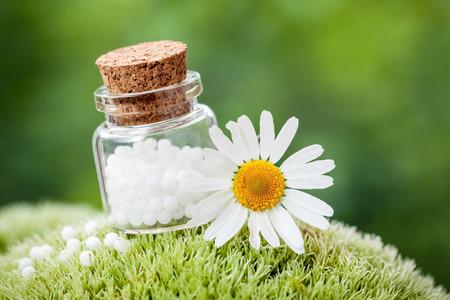 Fles van de homeopathie bolletjes en Daisy bloem op groene mos.