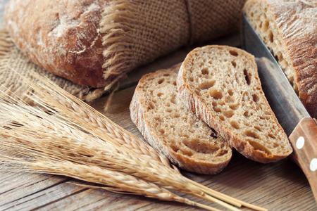 bolsa de pan: rebanada de pan de centeno y trigo nuevo en la mesa rústica. Foto de archivo