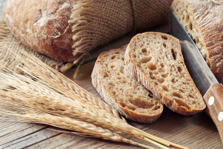 Vers sneetje brood en rogge oren op rustieke tafel.