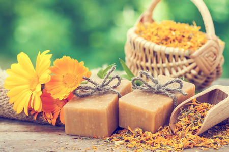 homemade style: Bars of homemade soaps and calendula flowers. Vintage stylized photo.